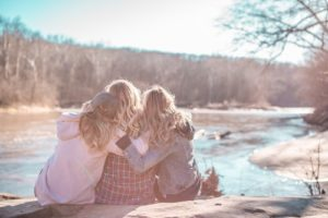 Three women hugging - reducing stress helps getting pregnant